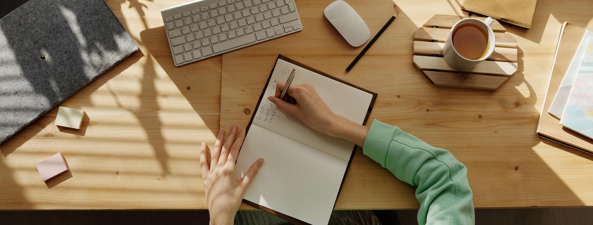 Hands on desktop writing in notebook