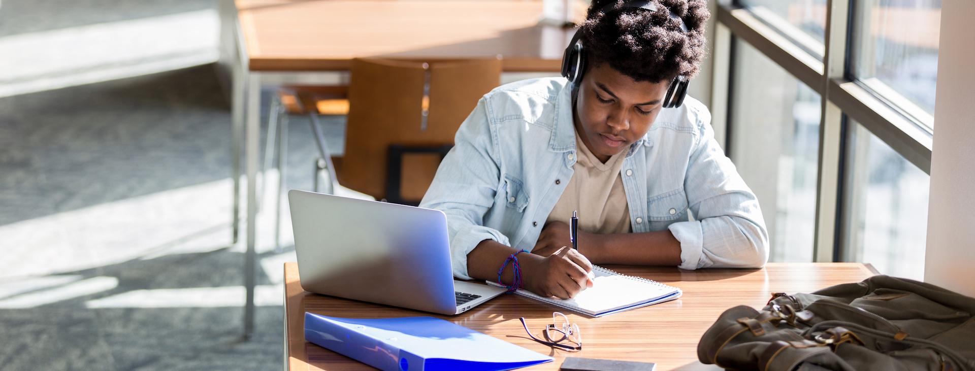 Teenage boy studies in school library