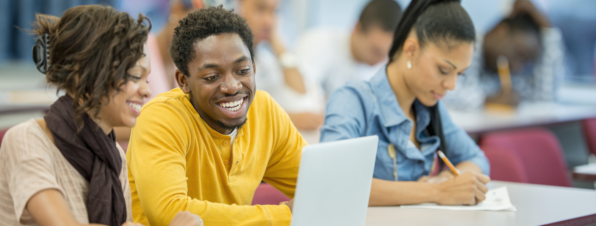 Students smiling looking at laptop
