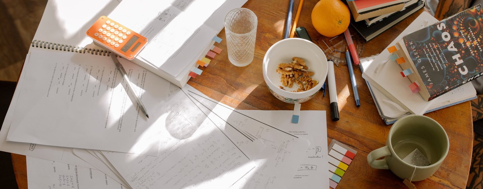 Papers, snacks, books and calculator spread out on a wooden table