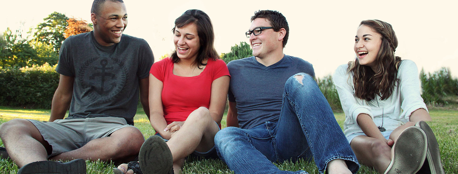 Four friends - two women and two men sitting together on a lawn.