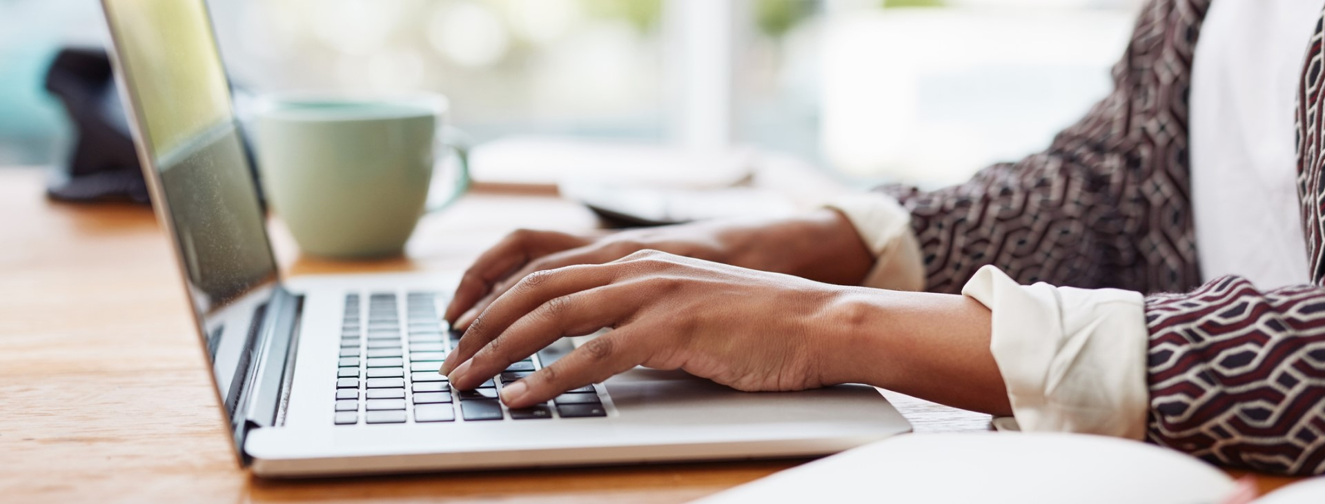 Person typing on a laptop keyboard.