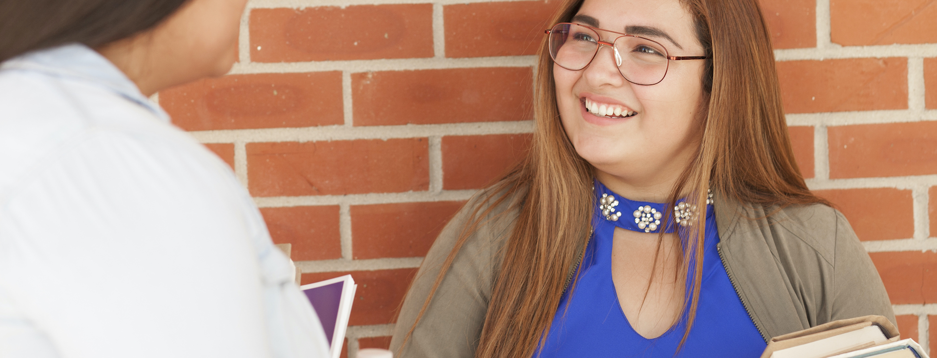Young person wearing glasses and blue top smiling