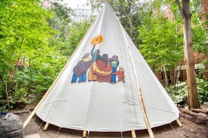 Artwork on tipi: six figures resembling a family, facing forward, embracing shoulder to shoulder. Figure in the middle holds up an eagle feather to the sun.