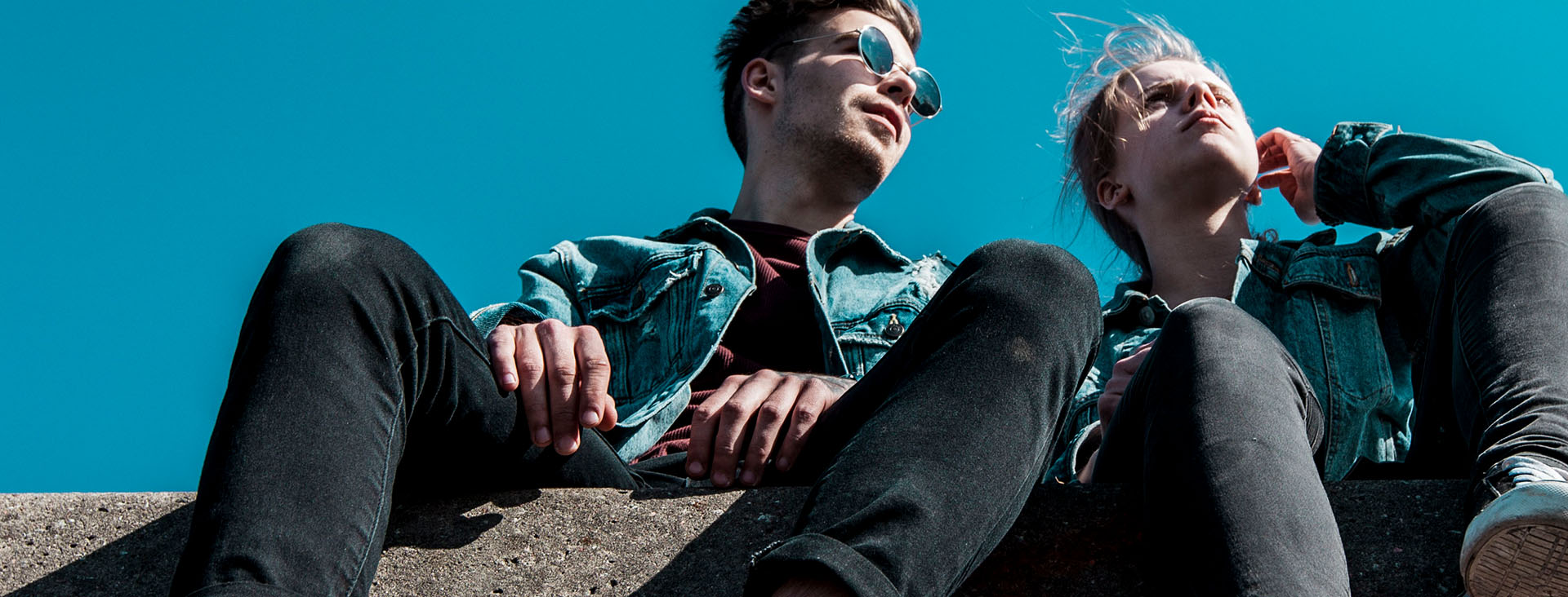 Two young people sitting on a stone against a blue sky
