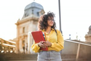 Young woman holding books on campus steps