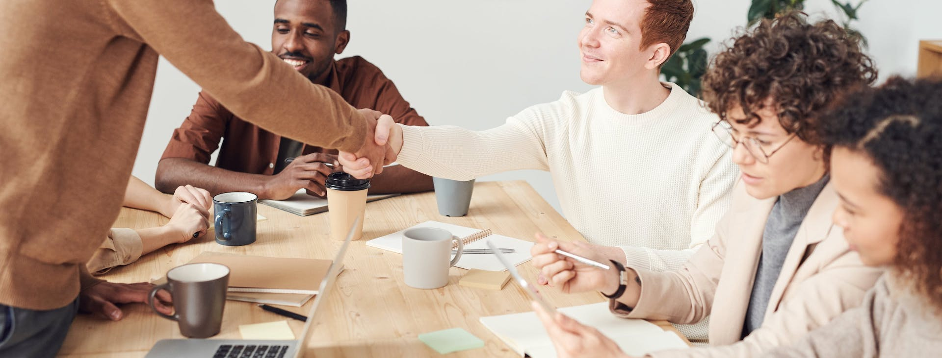 Group of five working together at table with two shaking hands