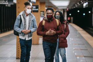 Students walking on subway platform wearing masks